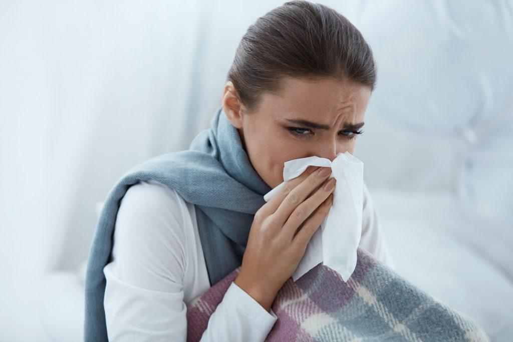 Woman sneezing into tissue