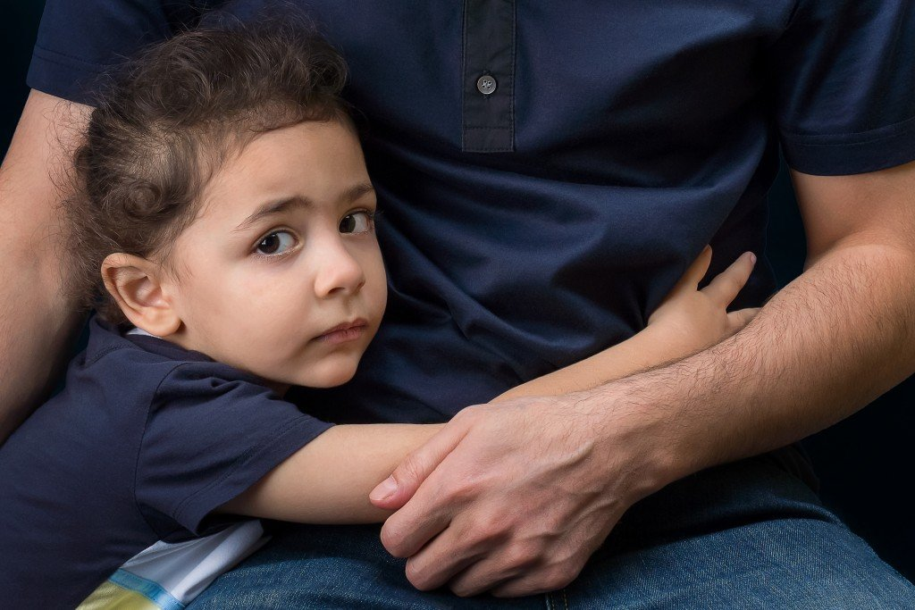 A little boy hugs his father's hand