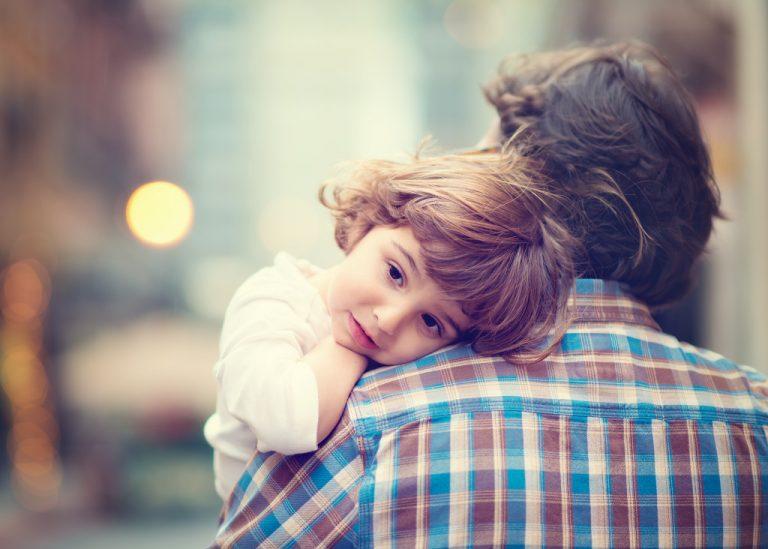 Baby resting his head on dad's shoulder