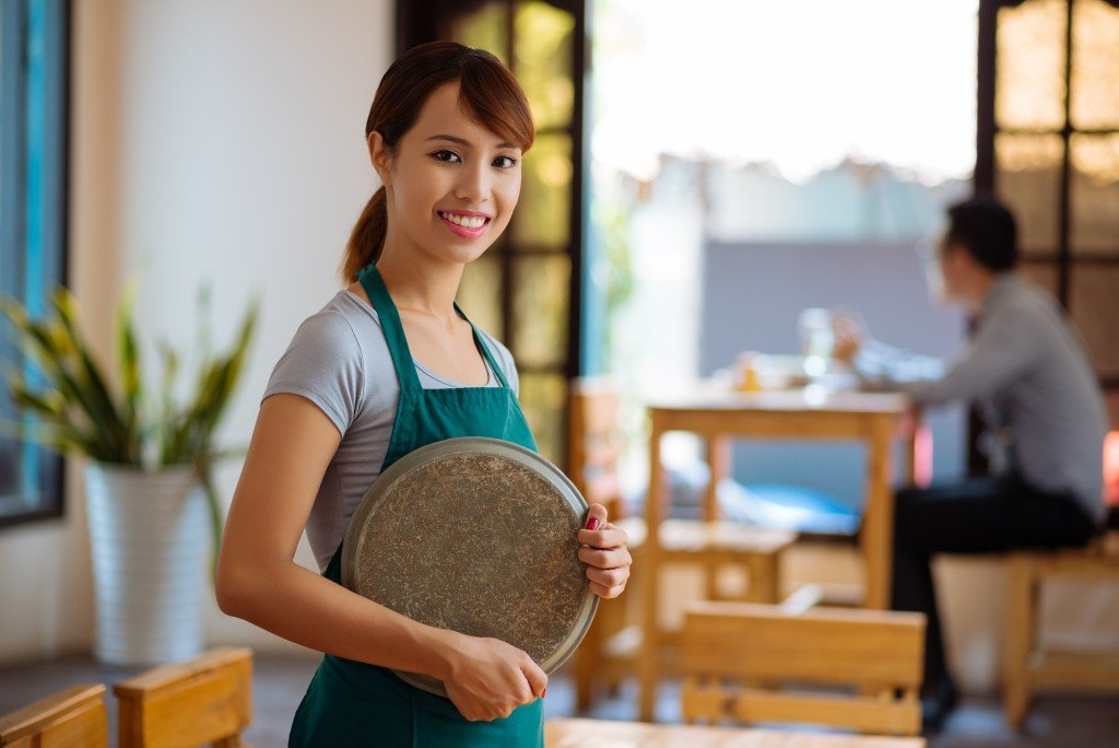 waitress with a tray standing in a cafe