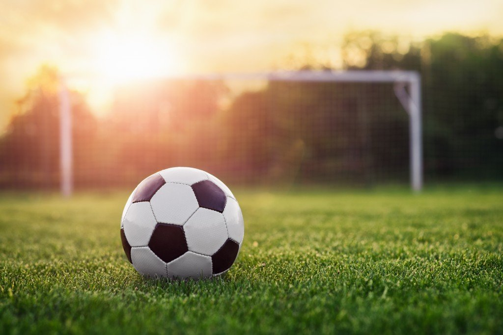 photography of a football in front of a goalpost