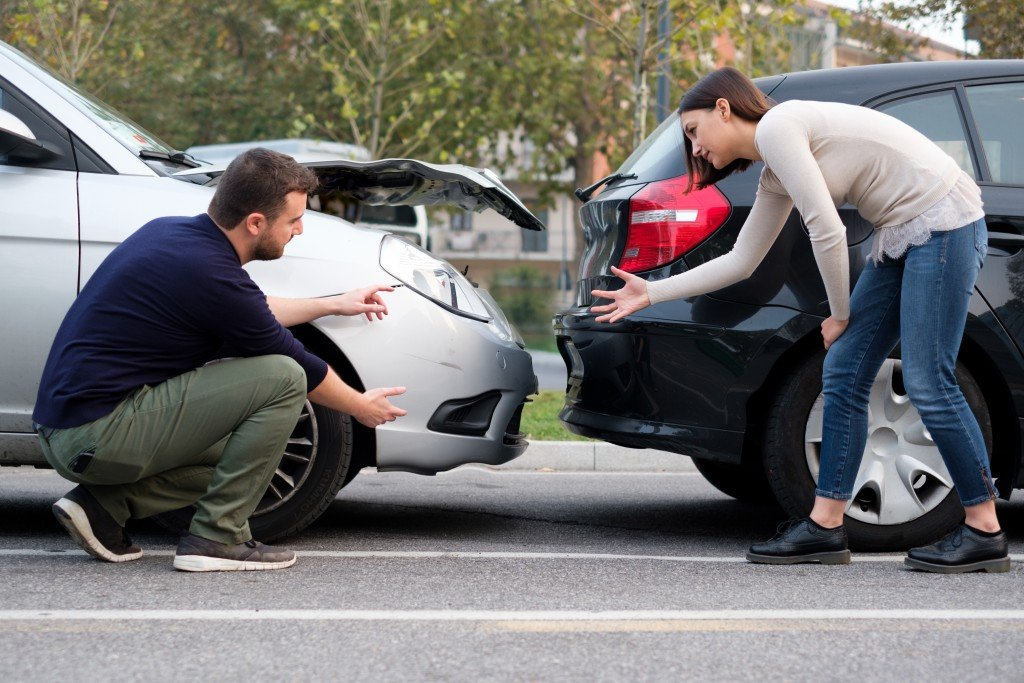 Two drivers arguing between a car accident