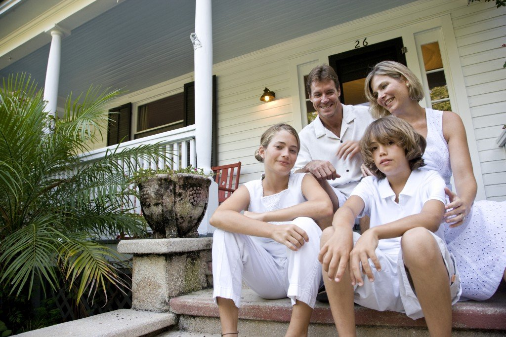 a family by the front steps of their house