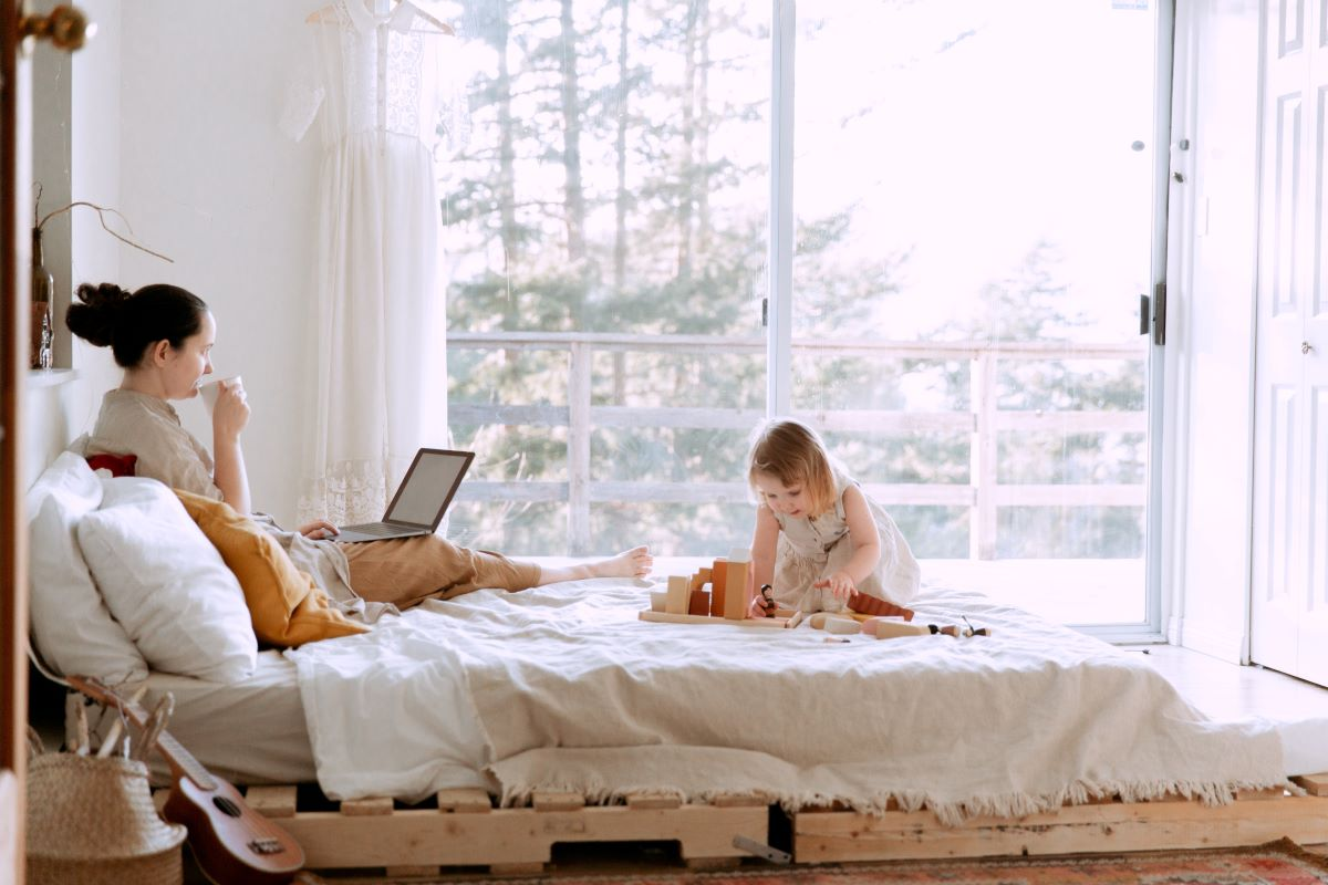 mother working in bed with daughter