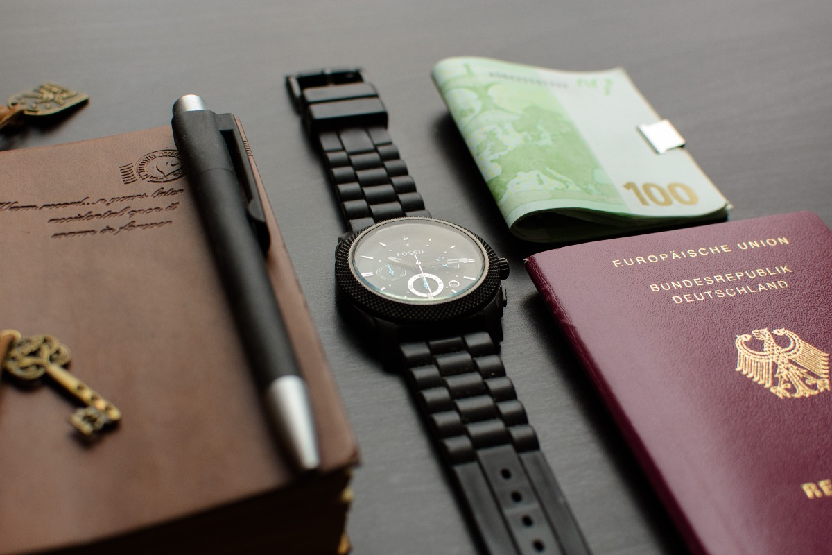 passport watch and notebook on table