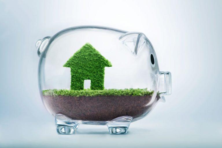 miniature house made of grass inside glass piggy bank