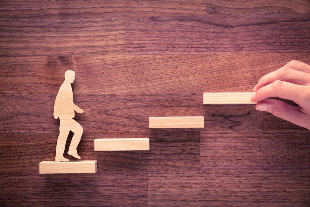 wooden figure of a man climbing up a wooden flight of stairs