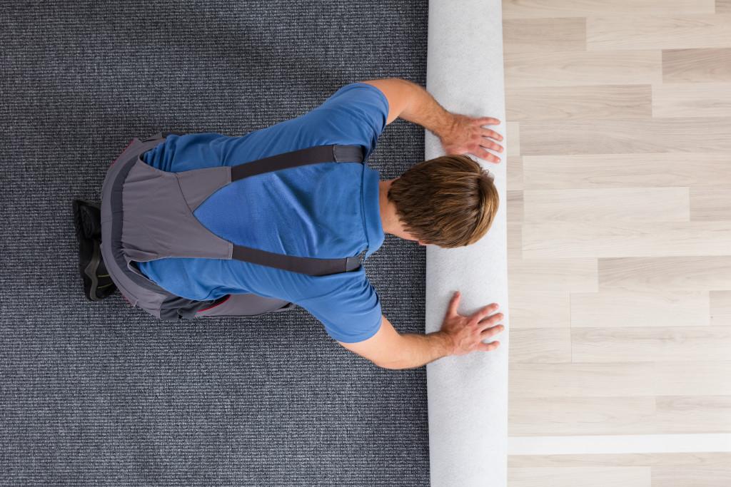 man installing a carpet